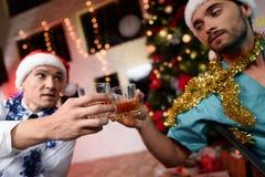 Dos doctores celebran el Año Nuevo en la oficina Tintinean los vidrios con el whisky Foto de archivo libre de regalías