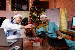 Dos doctores celebran el Año Nuevo en la oficina Tintinean los vidrios con el whisky Fotos de archivo libres de regalías
