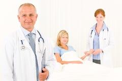 Dos doctores con el paciente que miente en cama Fotografía de archivo libre de regalías