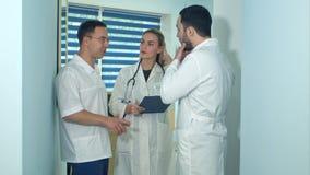 Dos doctores de sexo masculino que tienen discusión mientras que son femeninos cuidan la fabricación de notas Foto de archivo libre de regalías