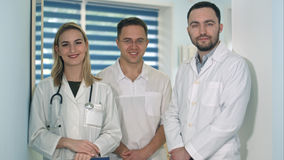 Dos doctores de sexo masculino y doctor de sexo femenino con el estetoscopio que sonríen a la cámara Imágenes de archivo libres de regalías