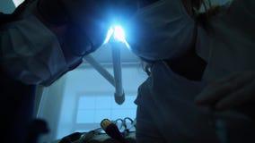 Dos doctores del dentista en máscara están sonriendo, sosteniendo un espejo de boca y un gancho, las vueltas la luz de la lámpara almacen de video