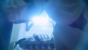 Dos doctores del dentista en máscara están sonriendo, sosteniendo un espejo de boca y un gancho, las vueltas la luz de la lámpara almacen de metraje de vídeo
