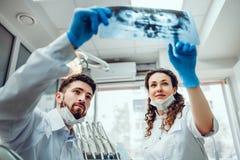Dos doctores del dentista que miran imagen del diente de la radiografía foto de archivo libre de regalías