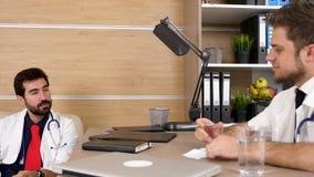 Dos doctores en la oficina que tiene una conversación agradable almacen de metraje de vídeo