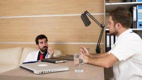 Dos doctores en oficina acogedora moderna que hablan el uno al otro metrajes