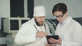 Dos doctores que consultan usando la tableta en la clínica 4K almacen de video