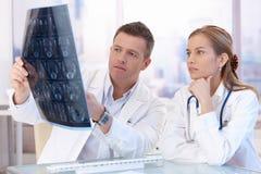 Dos doctores que estudian la consulta de la imagen de la radiografía Fotografía de archivo libre de regalías