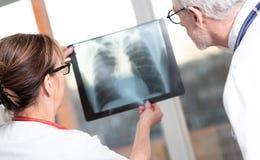 Dos doctores que examinan informe de la radiograf?a fotos de archivo libres de regalías