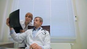 Dos doctores que examinan radiografías de los pacientes en oficina almacen de video