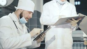 Dos doctores registrating datos en tableta y cuaderno en la clínica 4K almacen de video