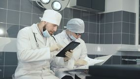Dos doctores registrating datos en tableta y cuaderno en la clínica 4K metrajes