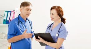 Dos doctores son diskussion algo en la clínica de la oficina, el doctor y la enfermera médicos, seguro médico fotografía de archivo libre de regalías