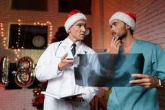 Dos doctores trabajan en el ` s Eve del Año Nuevo y discuten una radiografía que se lleve a cabo en manos Imagenes de archivo