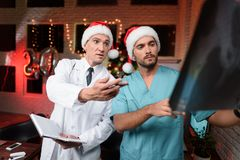 Dos doctores trabajan en el ` s Eve del Año Nuevo y discuten una radiografía que se lleve a cabo en manos Fotografía de archivo