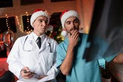 Dos doctores trabajan en el ` s Eve del Año Nuevo y discuten una radiografía que se lleve a cabo en manos Foto de archivo