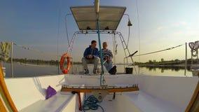 Dos dueños de un yate que se sientan y que hablan El navegar, actividades al aire libre almacen de metraje de vídeo