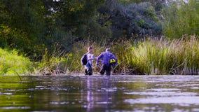 Dos ecologistas de los científicos en altas botas de goma que caminan en el agua del río del bosque almacen de video