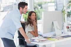 Dos editores de fotos que trabajan en su ordenador imagen de archivo