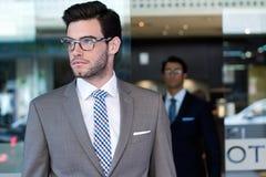 Dos ejecutivos jovenes que llegan el hotel Imágenes de archivo libres de regalías