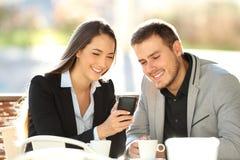 Dos ejecutivos que miran en la línea contenido en un teléfono Foto de archivo