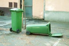 Dos el cubo de la basura plástico verde uno es mentira volcada en la calle Fotografía de archivo libre de regalías