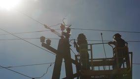 Dos electricistas que reparan los alambres eléctricos en un polo almacen de video