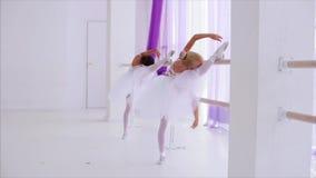 Dos elementos de la danza del funcionamiento de los niños de las bailarinas que se colocan cerca de soporte de la barra almacen de video