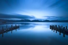 Dos embarcadero o embarcadero de madera y en un refle azul de la puesta del sol y del cielo del lago Foto de archivo