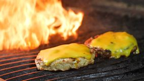 Dos empanadas de la hamburguesa con queso se asan a la parrilla en la parrilla, el queso se derriten bajo los efectos del calor,  metrajes