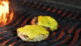 Dos empanadas de la hamburguesa y del queso se asan a la parrilla en la parrilla, el queso se derriten bajo los efectos del calor metrajes