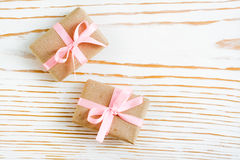 Dos empaquetaron el regalo con una cinta rosada en un fondo de madera blanco Imagen de archivo