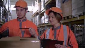 Dos empleados en workwear y cascos que discuten el trabajo en almacén cerca de las cajas metrajes