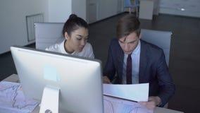 Dos empleados jovenes son trabajo, sentándose en la tabla con el ordenador en compañía, hombre y mujer grandes en ropa del negoci almacen de video