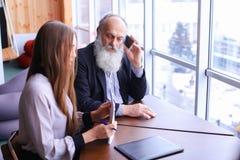 Dos empleados jovenes y charla del viejo hombre sobre el teléfono elegante para discutir p Fotos de archivo libres de regalías