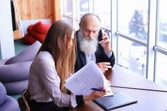 Dos empleados jovenes y charla del viejo hombre sobre el teléfono elegante para discutir p Imágenes de archivo libres de regalías