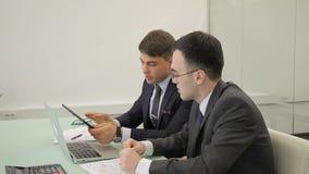 Dos empleados que hablan, sentándose en la tabla con el ordenador portátil y la tableta en oficina metrajes