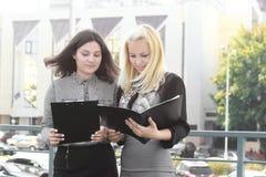 Dos empleados que leen los documentos que se colocan en el balcón de la oficina imagen de archivo libre de regalías