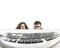 Dos empollones que miran fijamente un teclado fotografía de archivo