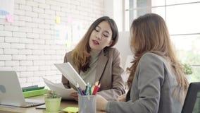 Dos empresarias asiáticas jovenes que trabajan junto en oficina en la pequeña empresa que se sienta leyendo un informe o un papel