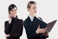 Dos empresarias atractivas jovenes con el teléfono celular y la carpeta foto de archivo