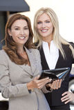 Dos empresarias con el ordenador de la tablilla Fotos de archivo