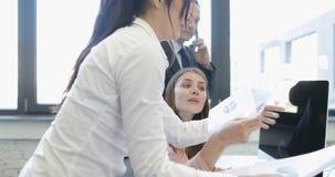 Dos empresarias discuten documentos studing de los informes mientras que jefe del hombre de negocios que hace llamada y que da el almacen de video