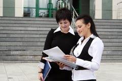 Dos empresarias felices con la carta de papel Imagenes de archivo