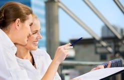 Dos empresarias felices con la carta de papel Imagen de archivo