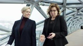 Dos empresarias femeninas son que caminan y de discusiones de negocio Son todos que trabajan en distrito financiero central Son almacen de metraje de vídeo