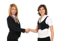 Dos empresarias jovenes están sacudiendo sus manos Foto de archivo libre de regalías