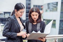Dos empresarias jovenes que miran en la carpeta de archivos del documento para analizar la circulación del beneficio o la rotura  imágenes de archivo libres de regalías