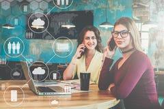 Dos empresarias jovenes que se sientan en café en la tabla y que hablan en los teléfonos celulares Fotos de archivo libres de regalías