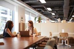 Dos empresarias jovenes que tienen entrevista informal en área de la cafetería en el día graduado de la evaluación del reclutamie imagenes de archivo